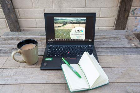 laptop on a table with a cup of tea and a notepad (Championing the Farmed Environment)