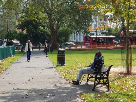 a woman skipping in a park with other park users sitting on a bench and walking © Tim Webb