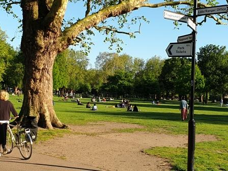 Signpost in a park with person on a bike and people sitting on the grass Credit: Landscape Institute