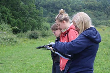 People standing in a field with clipboards doing a Phase 1 habitat mapping survey (Sue Searle)