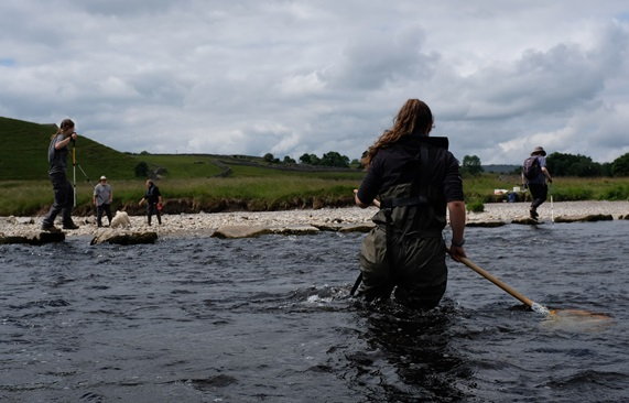people in waders carrying out sampling in river