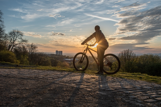 cyclist on bike sihouetted against a setting sun