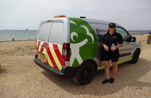 Sampling officer with water sample taken from Lepe beach in Hampshire (Environment Agency)