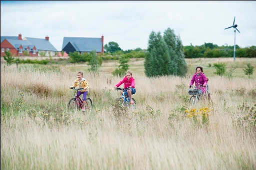 Children riding bikes on a meadow near housing at Cambourne © Matthew Roberts