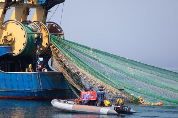 inflatable boat approached the stern of large trawler pulling nets