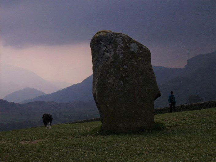 standing stone with collie and walker on either side against a moody purple sky (photo John Johnes)