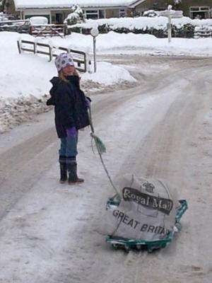 photo: child pulling a sledge loaded with mail bags