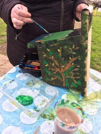 person painting a bird nestbox (Be Wild Buckfastleigh)