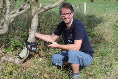 Frazer Coomber next to a tree with a camera trap on it (The Mammal Society)