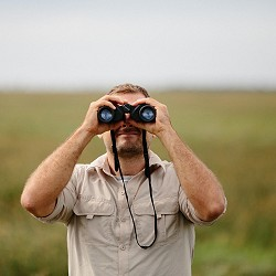 man looking through binoculars (image: StockSnap / pixabay)
