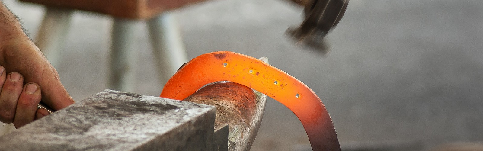 glowing red hot horseshoe over an anvil with hammer poised to strike (image: Jacqueline Macou / Pixabay)