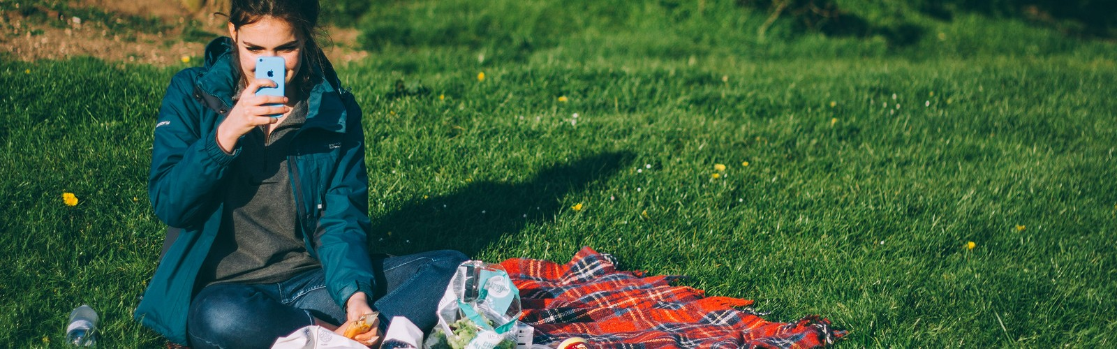 woman sitting on blanket having a picnic (image: Luke Porter on Unsplash)