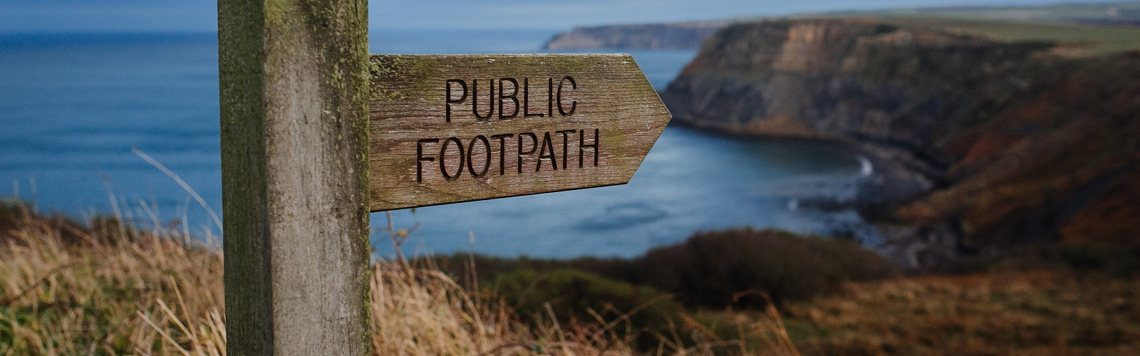 Public Footpath signpost on cliff overlooking a sea bay (image: Phil Hearing on unsplash)