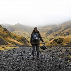 back view of person with rucksack and bags standing on a gravel path (image: Alexandre Godreau on unsplash)