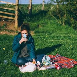 woman sitting on the grass having a picnic (image: Luke Porter on Unsplash)