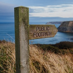 Public Footpath sign overlooking a sea bay (image: Phil Hearing on unsplash)