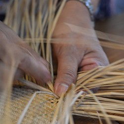 hands weaving reeds (image: Wei Cheng Wu on Unsplash)