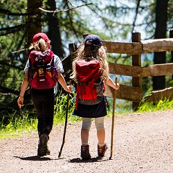 children wearing red rucksacks walking in the sunshine (image: pixabay)