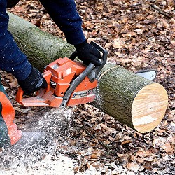 man using a chainsaw to cut a fallen tree (image: Hans Linde on unsplash)