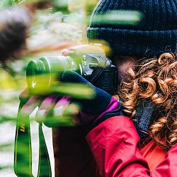 women wearing wooly hat and gloves photographing vegetation (image: Dan Smedley on Unsplash)